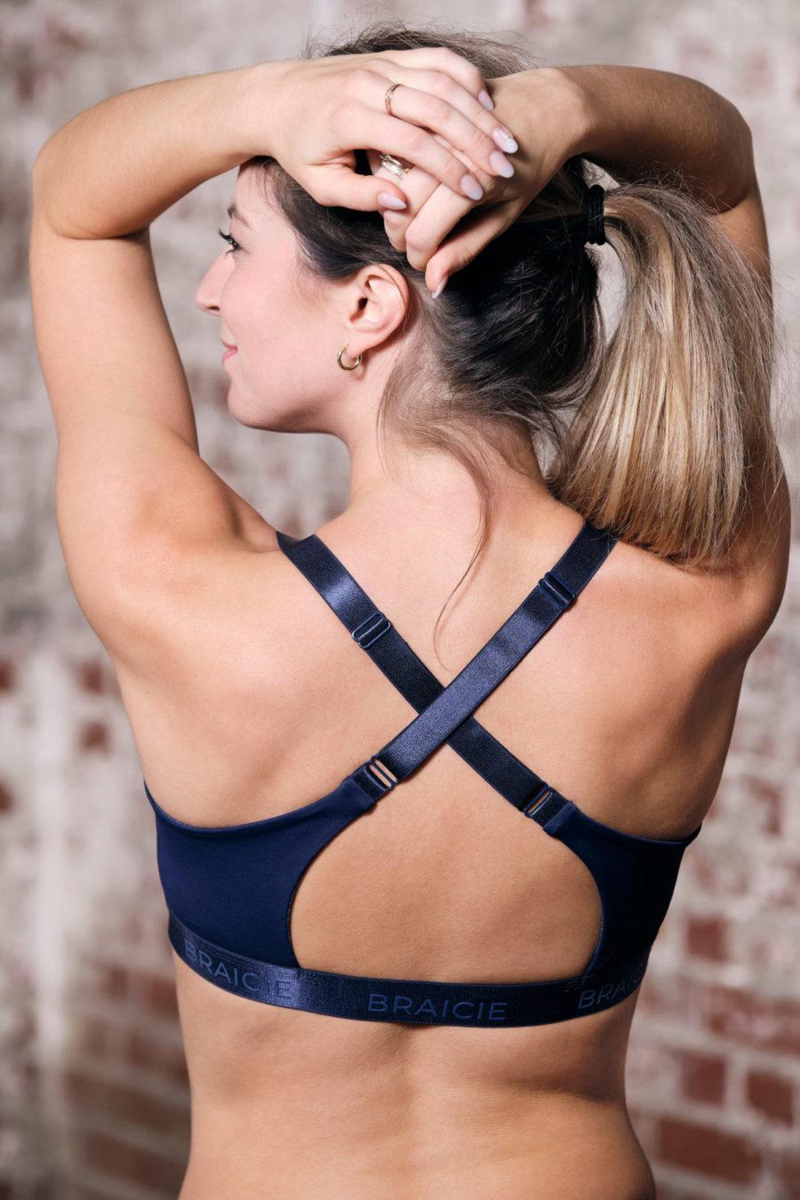 Rückenansicht einer Frau im BRAICIE Empower Sport-BH in blau