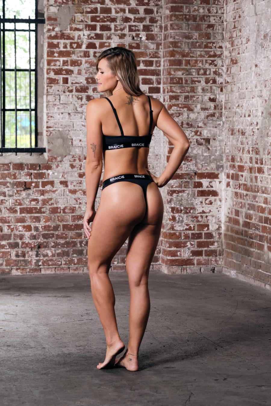 Ganzkörper Rück-Ansicht einer Frau im Sport-BH und Sport-String in schwarz