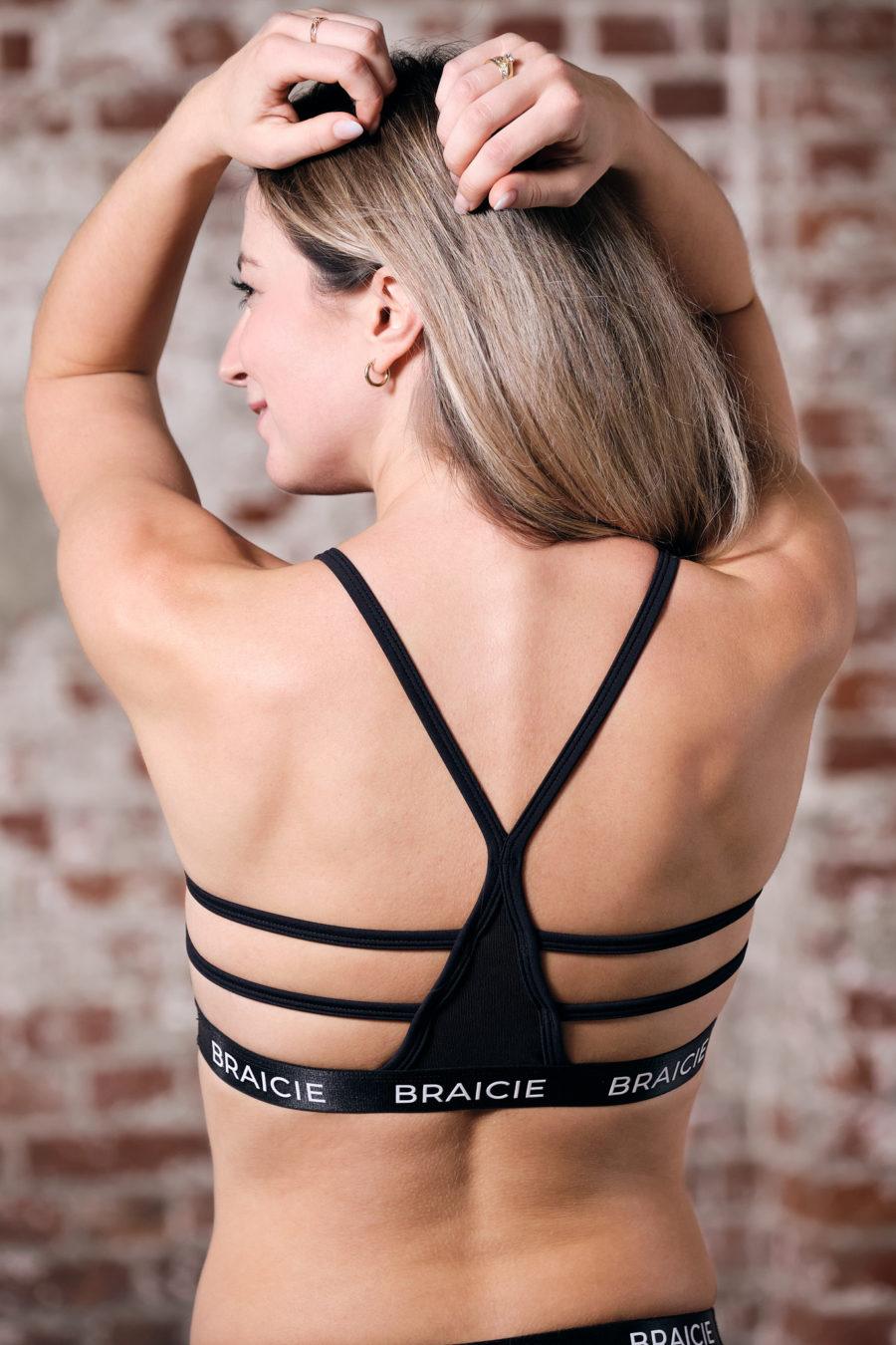 Rückenansicht einer Frau im BRAICIE Stripes Sport-BH in schwarz