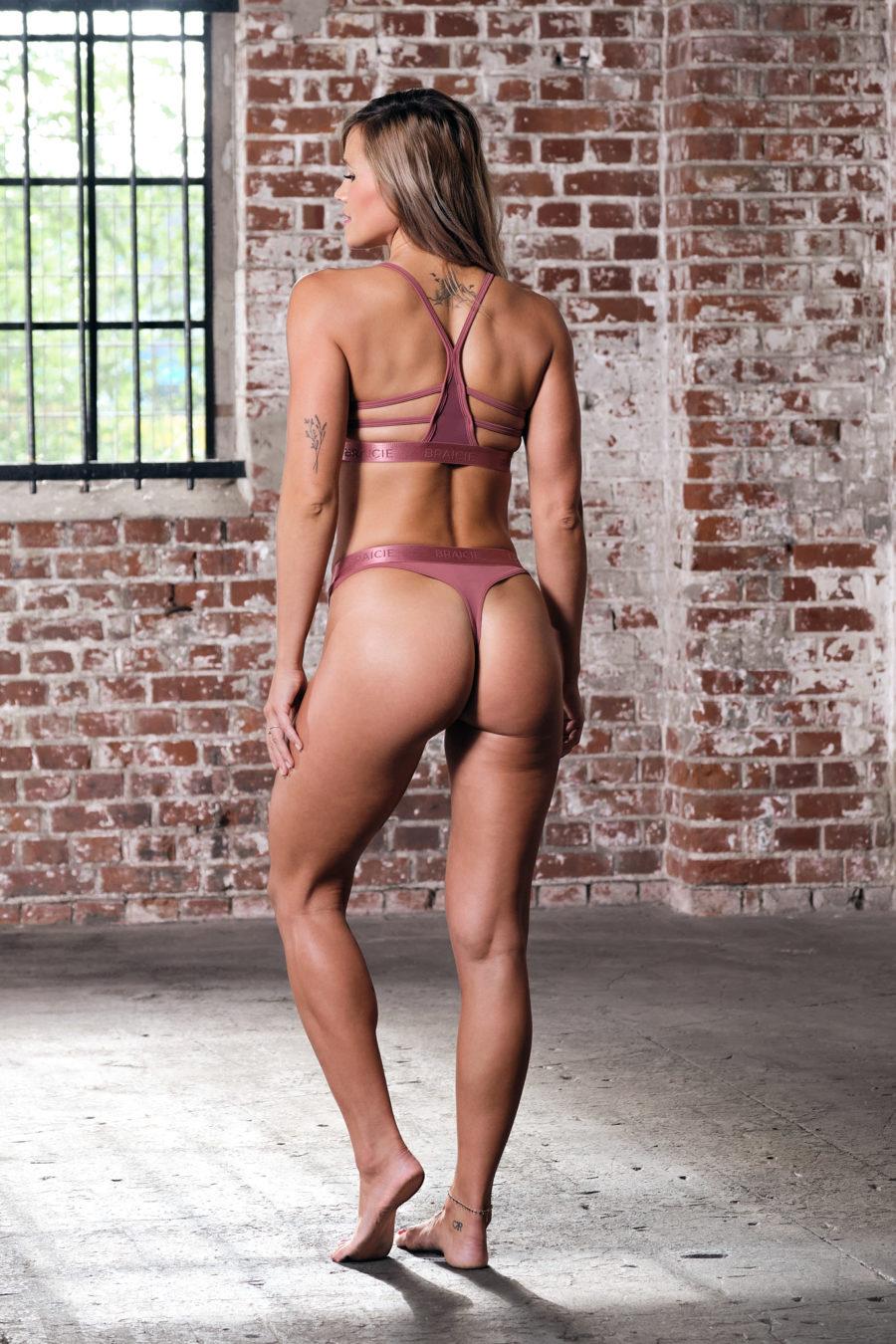 Ganzkörper Rück-Ansicht einer Frau im Sport-BH und Sport-String in rose